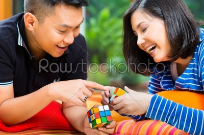 stock photo: asian couple at home playing with magic cube-Raw Stock Photo ID: 44921
