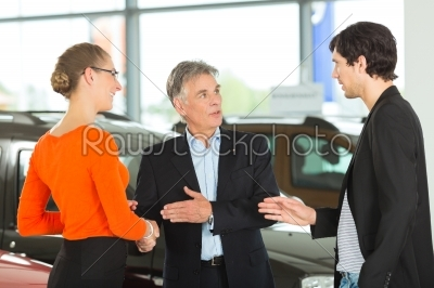 stock photo: mature man handshaking with young couple and auto in car dealership-Raw Stock Photo ID: 45035