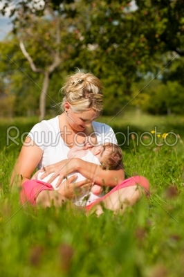 stock photo: mother nursing baby on meadow-Raw Stock Photo ID: 40208