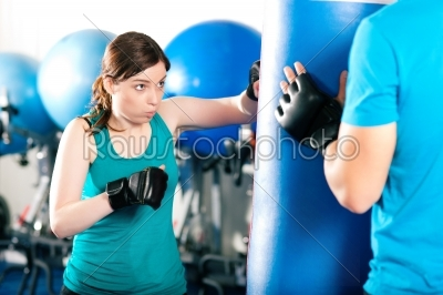 stock photo: woman boxer hitting the sandbag her trainer is assisting-Raw Stock Photo ID: 40628