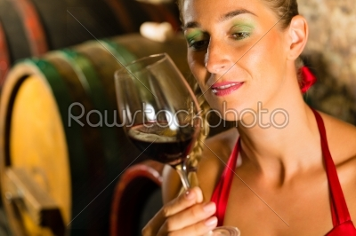 stock photo: woman looking at red wine glass in cellar-Raw Stock Photo ID: 46227