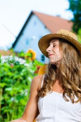 stock photo: woman tanning in her garden on lounge chair-Raw Stock Photo ID: 42504