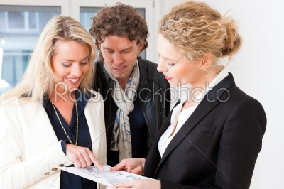 stock photo: young realtor explaining ground plan to couple-Raw Stock Photo ID: 43422