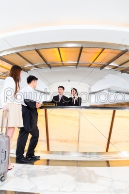 stock photo: asian chinese couple arriving at hotel front desk-Raw Stock Photo ID: 49613