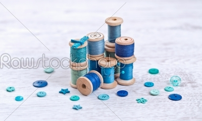 stock photo: collection of spools  threads in blue aqua colors arranged on a white wooden background-Raw Stock Photo ID: 68387