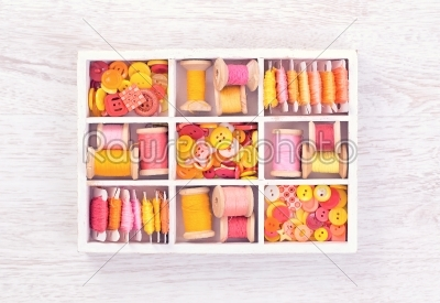 stock photo: collection of yellow red pink spools  threads  arranged in a white wooden box-Raw Stock Photo ID: 68382