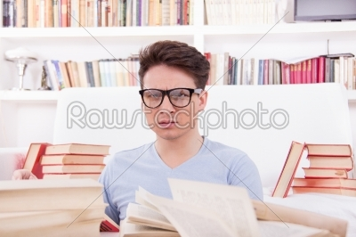 stock photo: confused student with glasses studying surrounded by books-Raw Stock Photo ID: 52641