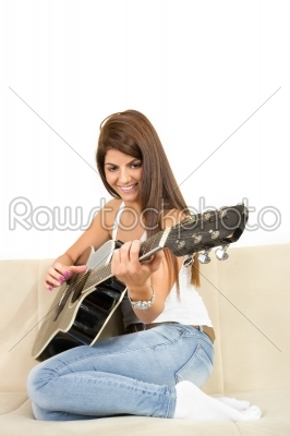 stock photo: pretty girl playing guitar on the sofa-Raw Stock Photo ID: 53996